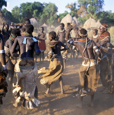 ETH2365 A lively Nyag'atom dance is enjoyed by villagers in the late afternoon. The elevated houses in the background are both homes and granaries, which have been built to withstand flooding when the Omo Riv...