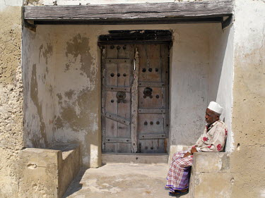 KEN5344 A Swahili man sits on a stone bench at the entrance to the compound of a large old house with a massive beam and decorated wooden doors.  Like most others in Faza village, the house is made of coral r...