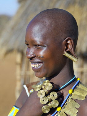 A Datoga woman in jovial mood. The traditional attire of Datoga women includes beautifully tanned and decorated leather dresses and coiled brass armbands, necklaces, earrings and rings. Yellow and li...
