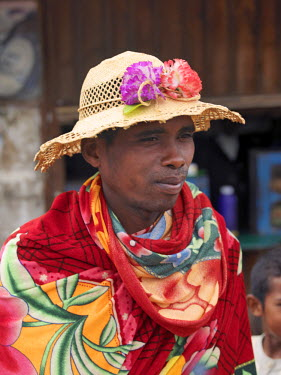 A Malagasy man wears a locally made hat decorated with artificial flowers.Madagascar is well known for the outstanding variety and styles of its local hats, which vary considerably from region to reg...