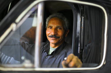 EGY1326 A mechanic sits inside a car at his garage in the district of Zamalek, Cairo, Egypt.