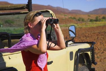 NAM3473 A tourist scans the horizon with binoculars while tracking rhino on the Palmweg concession in Damaraland, Namibia. (MR)
