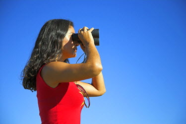 NAM3519 A young woman tourist scans the horizon with her binoculars. (MR)
