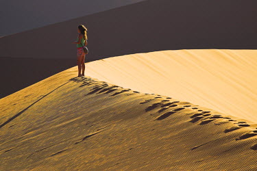 NAM3515 A young woman walks across the dunes at sunset at Sossusvlei, Namibia