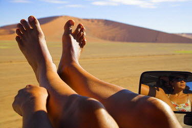 NAM3514 A young woman relaxes with her feet out of the window on the drive to the giant sand dunes at Sossusvlei, Namibia.