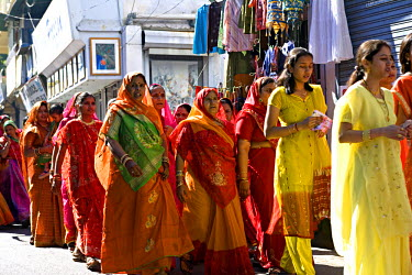 IND5384 Women take part in a wedding procession in Udaipur, Rajasthan. India