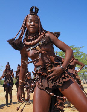 NAM3539 Himba women perform the otjiunda dance, stamping their feet, clapping and chanting while one of them gyrates in the centre of the circle. Their bodies gleam from a mixture of red ochre, butterfat and...