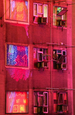 CH1487 The neon lights of Kowloon reflected in the windows of apartment blocks, Hong Kong.
