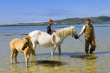 SCO8826 Gordon Muir, stalker and ghillie at Glen Batrick Lodge, leads young guest from the lodge along the shore of Loch Tarbert on a Highland pony