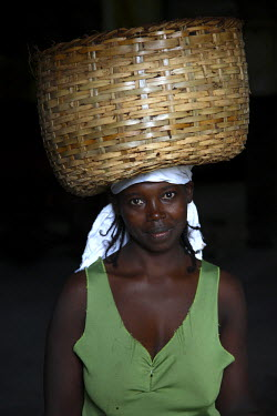 SAO1052 A Sao Tomense woman carries a basket full of cocoa beans at the cocoa processing plant in Agua Ize a small Sao Tomense village. Cocoa is the country's chief export. Sao Tome and Principe is Africa's s...
