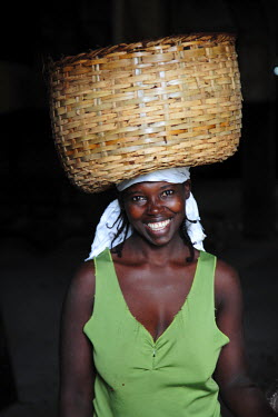SAO1051 A Sao Tomense woman carries a basket full of cocoa beans at the cocoa processing plant in Agua Iz̩, a small Sao Tomense village. Cocoa is the country's chief export. Sao Tom̩ and Princip̩ is Africa...
