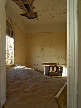 NAM3598 A scene in the deserted diamond-mining town of Kolmanskop, which was abandoned more than fifty years ago.  The place is now a ghost town where sand from the surrounding desert has encroached into all...