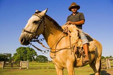 BRA0149 Young Pantanal cowboy astride horse on ranch area near Campo Grande, Pantanaladventure