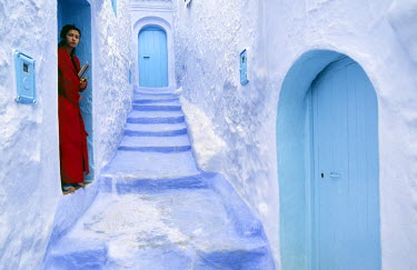 MOR1766 A local woman steps out into the whitewashed streets of the Rif Mountains town of Chefchaouen. The distinctive white and blue colour scheme was first introduced by Jewish refugees fleeing Spain in the...