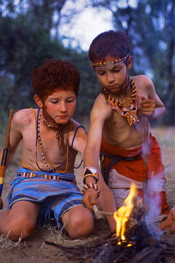 KEN1388 Children dressed as Samburu warriors make fire on a Cheli & Peacock family mobile safari.