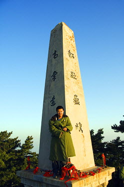 CH1850 A man in green army jacket on a monument on the top of Mount Hua, a granite peaked mountain (2160m) in the Shaanxi Province, China