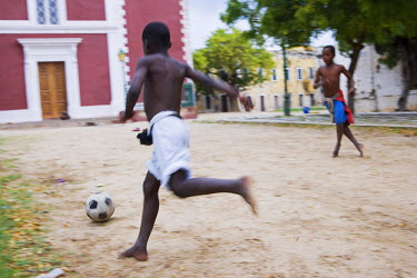 MOZ1242 Boys play football among the crumbling colonial mansions on Ilha do Mozambique