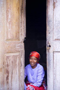 MOZ1235 A woman looks out from her doorway on Ilha do Mozambique