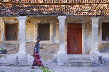 MOZ1181 A woman in front of an old Portuguese villa on Ibo Island, part of the Quirimbas Archipelago, Mozambique.