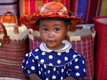 A young girl beside a road-side stall which is offering for sale brightly coloured raffia baskets and hats near Antananarivo, capital of Madagascar.