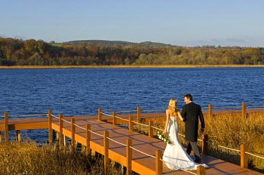 ENG8569 United Kingdom, Northern Ireland, Fermanagh, Enniskillen. Bride and groom walk arm in arm along the pontoon during their wedding at the Lough Erne Golf Resort Hotel (MR).
