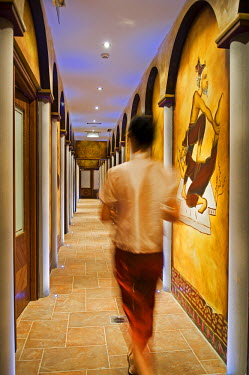 Northern Ireland, Fermanagh, Enniskillen. Thai therapist walks along the corridor of the spa at the Lough Erne Golf Resort (MR).