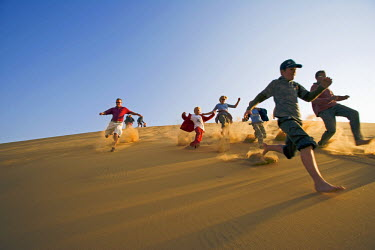 Namibia, Erongo Region, Swakopmund. A group of friends run down the steep face of a coastal dune kicking up sand and enjoying themselves. (MR).