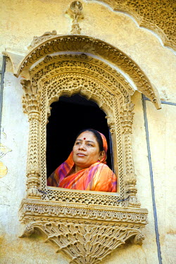 IND5677 India, Rajasthan, Jaiselmer, Patwon ki Haveli. Traditionally dressed dressed lady looks out of one of the heavily decorated windows in the in one the city's best preserved Havelis.