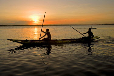 BRA0394 Brazil, Bahia, Barra de Serinhaem.  Fishermen returning to shore at sunset in thier dug out canoe.