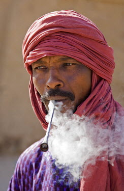 Mali, Timbuktu. A Tuareg man smokes a traditional metal pipe in Timbuktu.