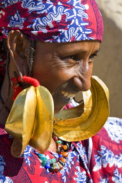MAL0554 Mali, Mopti. A Fulani Woman wearing large 14-carat gold earrings. Kwottenai Kanye earrings are either a gift from her husband or inherited on the death of her mother. The top of each earring is bound...