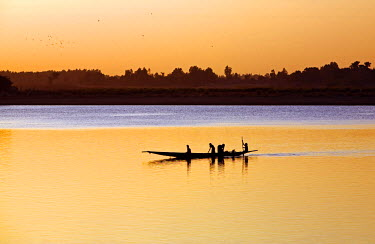 Mali, Mopti. At sunset, a boatman in a pirogue ferries passengers across the Niger River to Mopti.