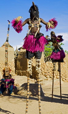 MAL0522 Mali, Dogon Country, Tereli. Masked stilt dancers wearing coconut shells as breasts perform at the Dogon village of Tereli. Tereli is situated among rocks at the base of the spectacular 120-mile-long...