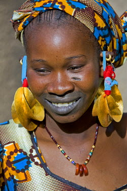 MAL0446 Mali, Senossa. A Peul woman wearing fine gold earrings which will have been given to her as a gift from her husband on her wedding or sometimes inherited upon the death of her mother. The scar on her...