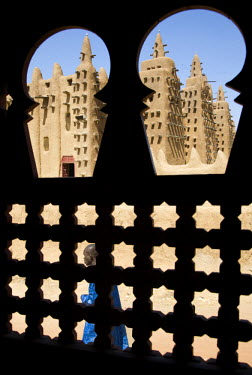 Mali, Djenne. The Great Mosque of Djenne from a traditional Moroccan-style latticed window. Constructed in 1907 on the foundations of a 13th century mosque built by King Koy Konboro, the 26th ruler of...
