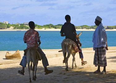 KEN5618 Kenya, Lamu Island, Shela. Two young men on donkeys ride past a Muslim man at Shela pier.