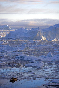 GRN1059 Greenland, Ilulissat, UNESCO World Heritage Site Icefjord.  A boat navigates its way through the scattered icebergs of the Icefjord with a massive berg providing a towering backdrop in the evening lig...