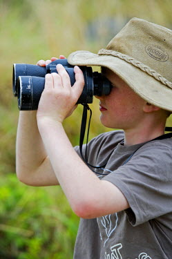 KEN5765 Kenya, Masai Mara National Reserve. Young boy on safari in the Masai Mara looking through binoculars (MR).