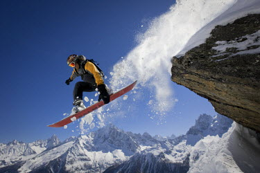 A snowboarder jumps off a rock at Le Brevent, Chamonix, France.