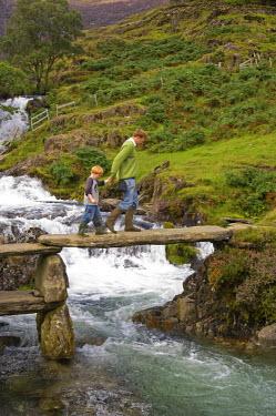 WAL6808 Wales, Conwy, Snowdonia. Man leads a boy across a rustic bridge over the Afon Cwm Llan alongside the Watkin Path on the route into Snowdon