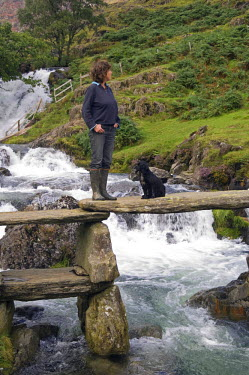 WAL6812 Wales, Conwy, Snowdonia.  Woman and dog on a rustic bridge over the Afon Cwm Llan alongside the Watkin Path on the route into Snowdon (MR)