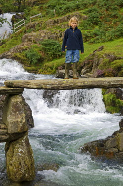 WAL6814 Wales, Conwy, Snowdonia. Child standing on a rustic bridge over the Afon Cwm Llan alongside the Watkin Path on the route into Snowdon