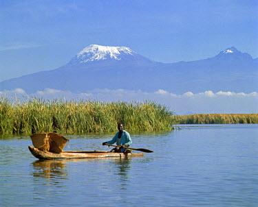 KEN5958 Kenya, Taveta, Lake Jipe. A fisherman paddles his dugout canoe across Lake Jipe with Mount Kilimanjaro in the background.