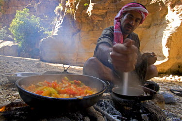 JOR0239 Jordan, Petra, Wadi Daphna. A local beduin guide dressed in traditional clothing prepares a lunch time meal over an open fire in the dead chasm within Wadi Daphna. (MR)