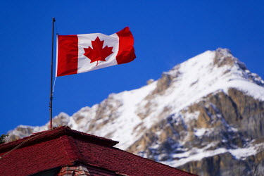 CA08109 Canadian flag flying on rooftop next to Bow lake,  Banff-Jasper National Parks, Alberta, Canada