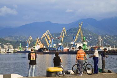 GG01024 Georgia, Black Sea Coast, Batumi, Men fishing at seafront
