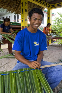 MI01009 Young Palauan boy weaving a roof with Pandanus leaves, Koror High School, Palau, Micronesia (MR)