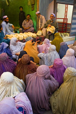 PK02046 Local women receiving bread, Peshawar bazaar, Peshawar, Pakistan