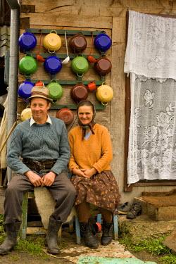 RM01216 Romania, Maramures, village couple outside their house