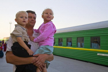 TR01026 Turkmenistan, Ashgabat, (Ashkhabad), Train station, Father holding his children on platform
